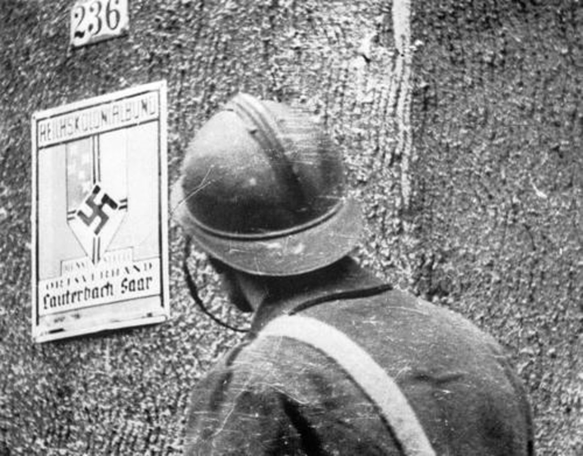 A French soldier looking at a Nazi sign in a captured village.