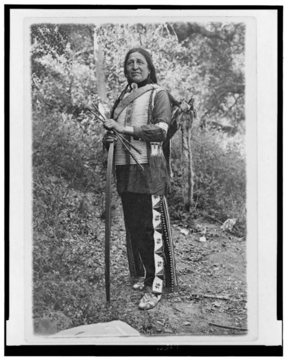 Chief Standing Bear (possibly Luther Standing Bear) full-length portrait, standing, facing slightly left, holding bow and arrows.