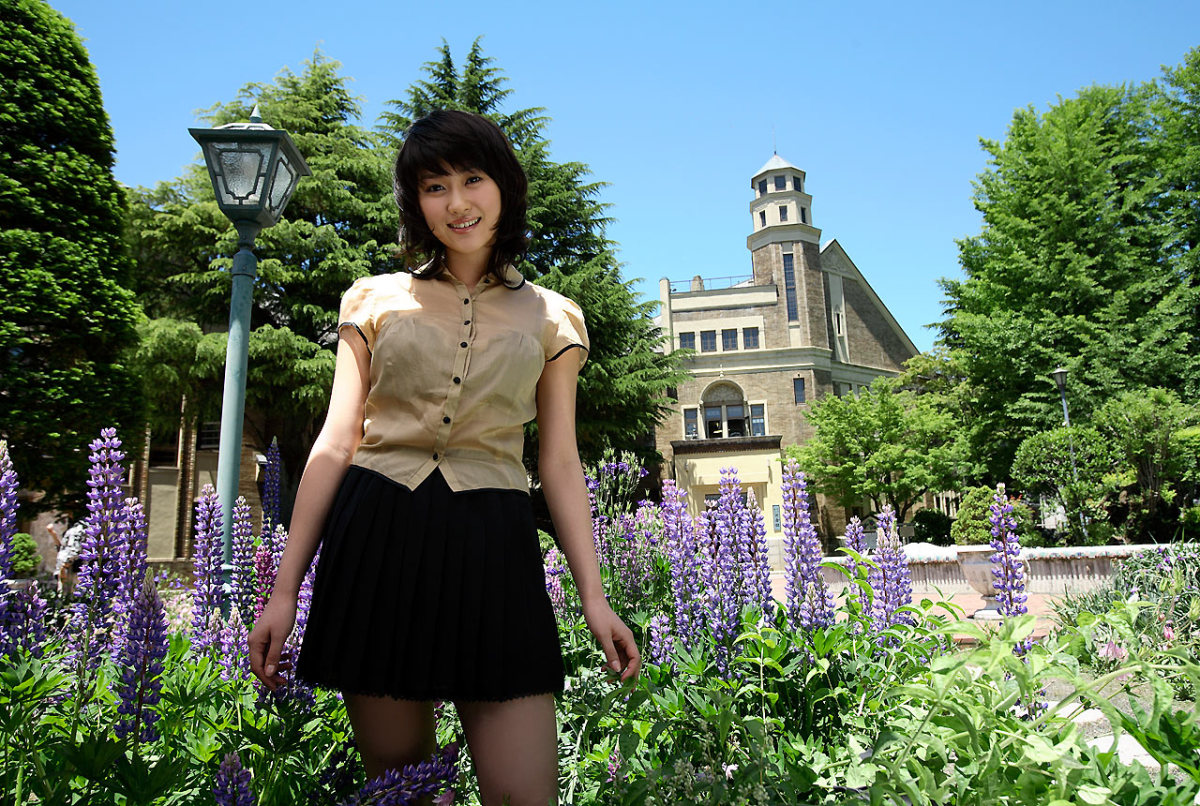 Mikie Hara stands in a very beautiful garden.