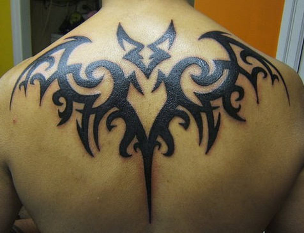 This tribal-style bat tattoo is large, centered, and super-stylized.