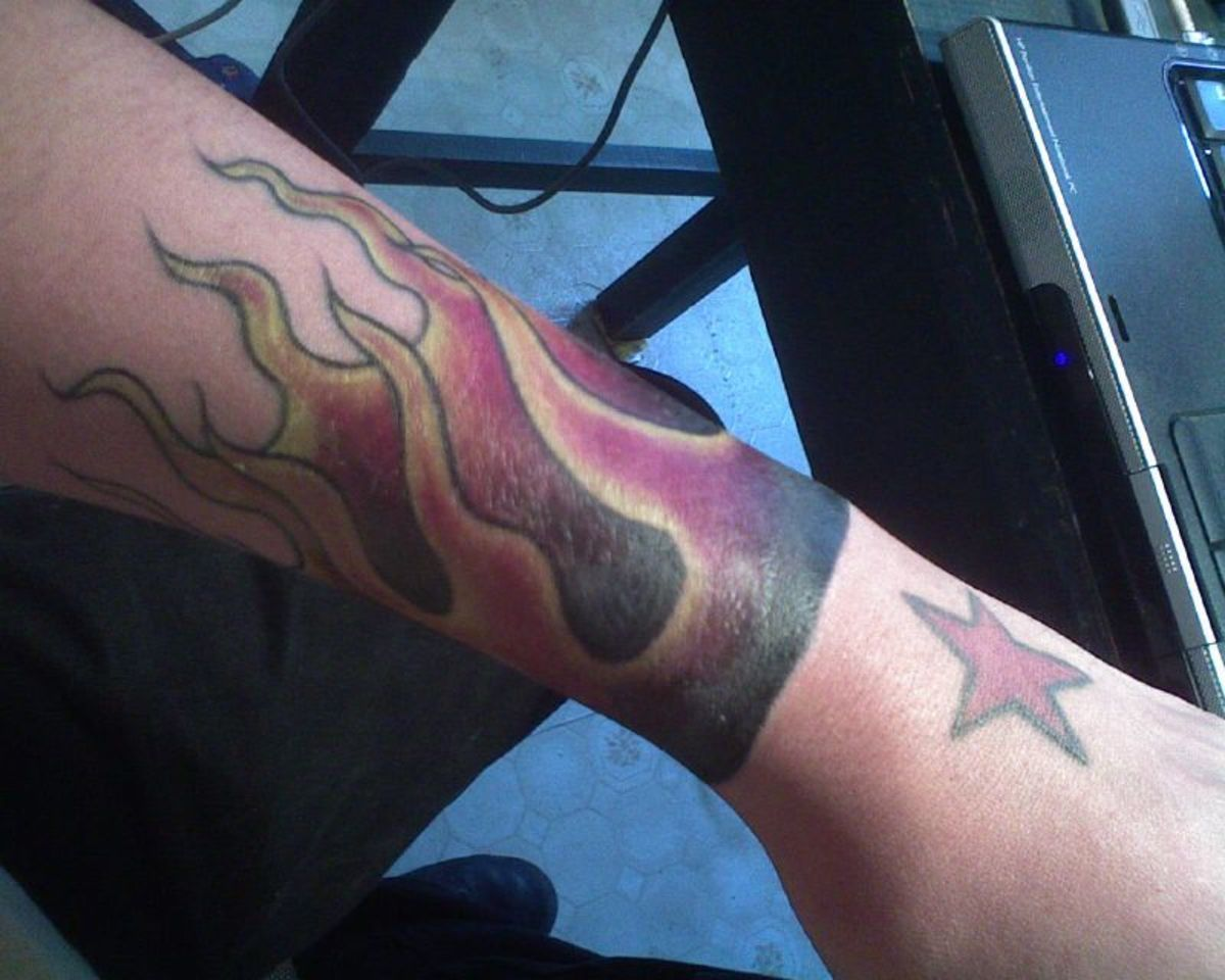 An arm tattoo of rising flames.