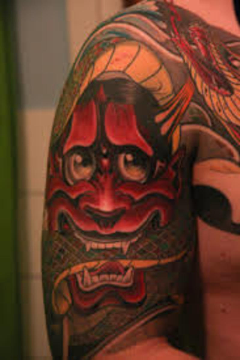 A red hannya tattoo with a snake between her teeth.