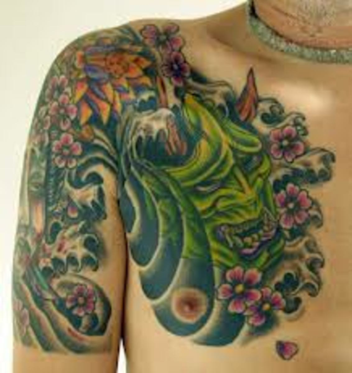 Another green hannya tattoo with flowers and waves.