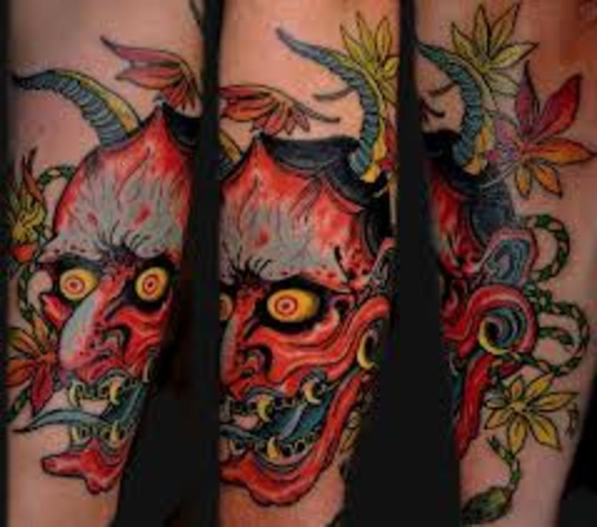 A vibrant red hannya mask tattoo.