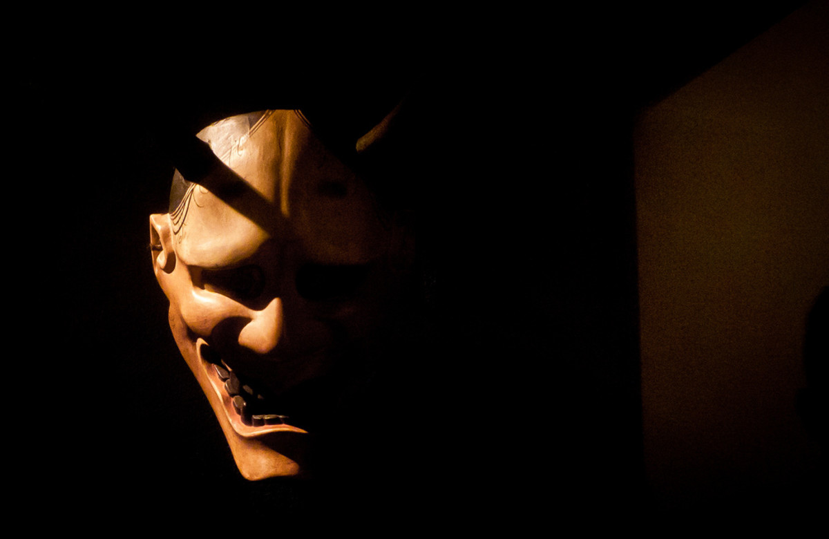 A carved hannya mask in dramatic shadow.