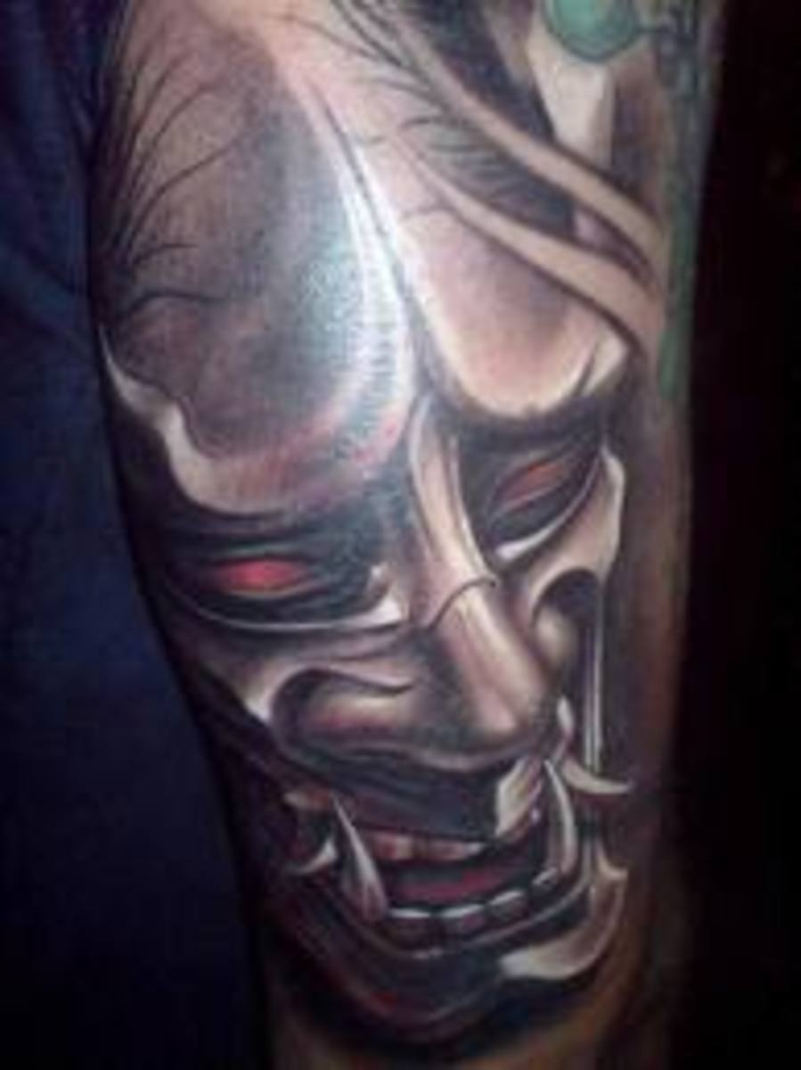 A red-eyed hannya tattoo with almost a metallic appearance.