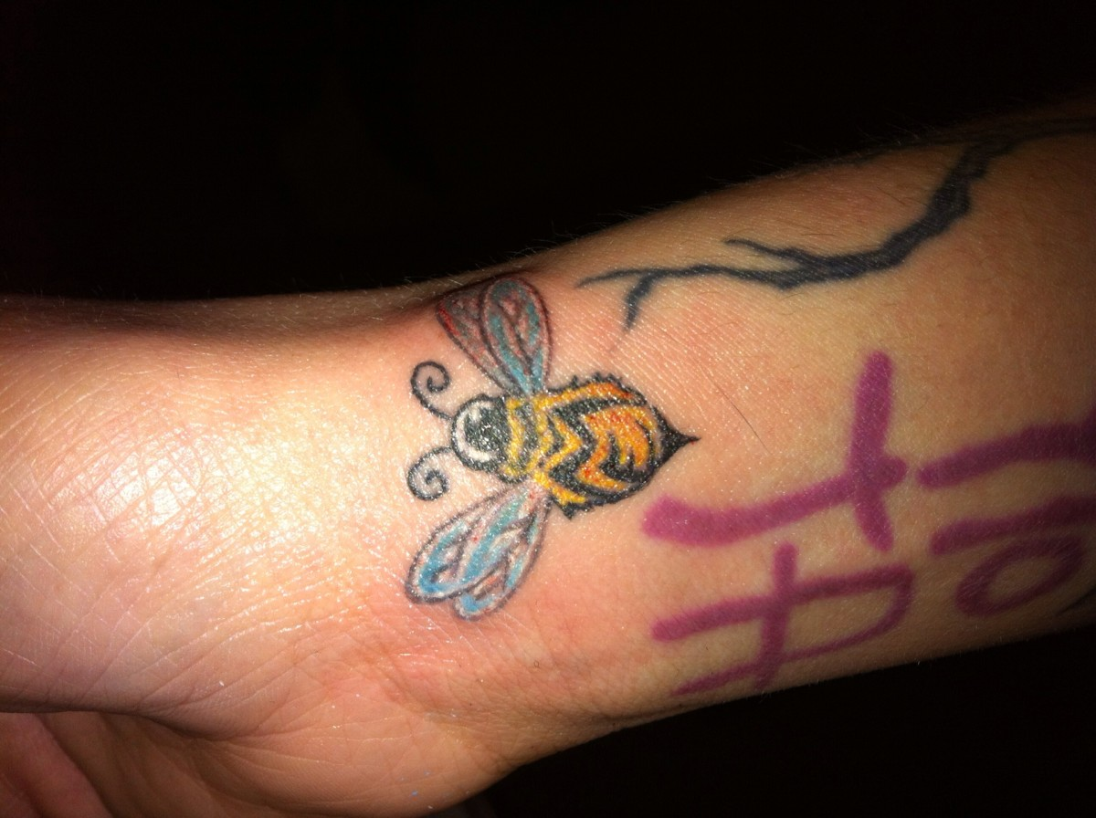 """A bee with the word """"ME"""" printed on it."""