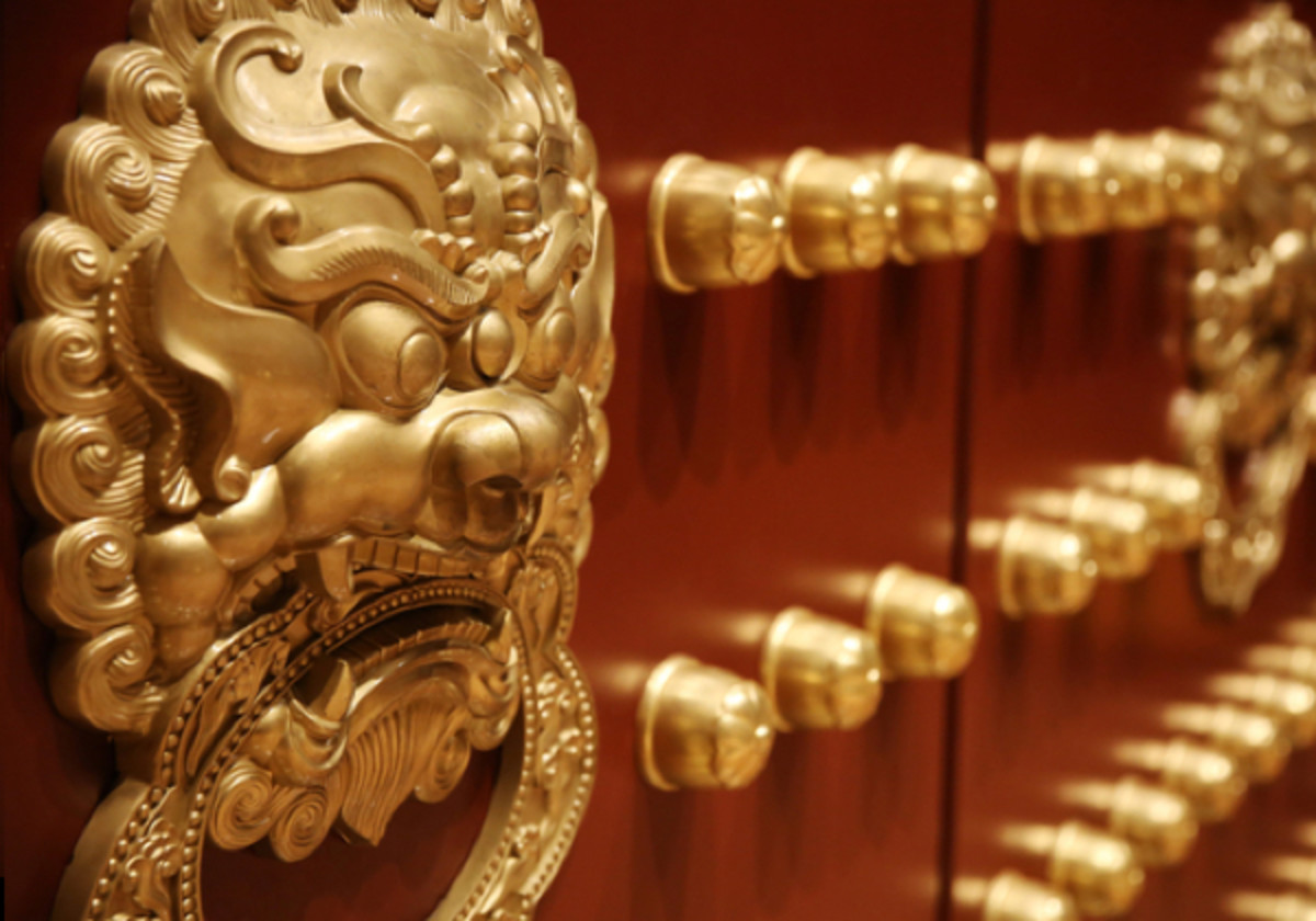 Bronze, Chinese lion head door knocker on a traditional wooden door.