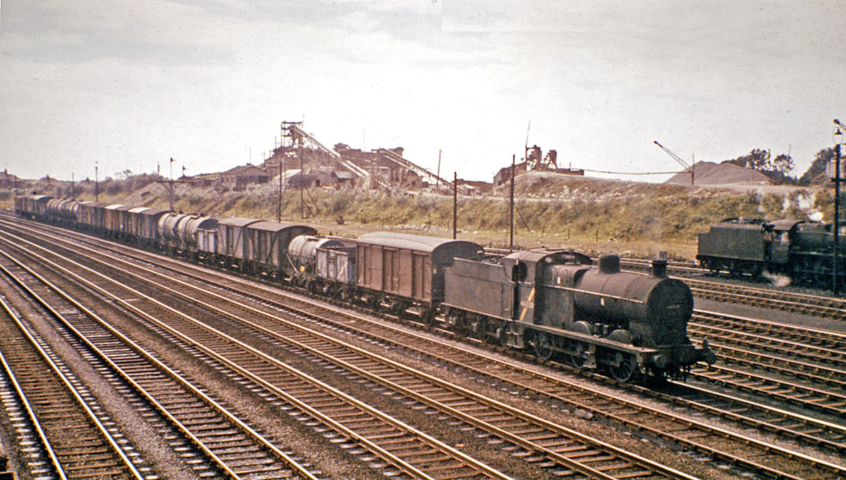 Goods... often overlooked, under-represented on layouts with expresses whizzing past  The humble 0-6-0 and its workload. An ex-Midland Railway 0-6-0 mixed freight locomotive clanks past an industrial north-western backdrop with a lengthy trip-working