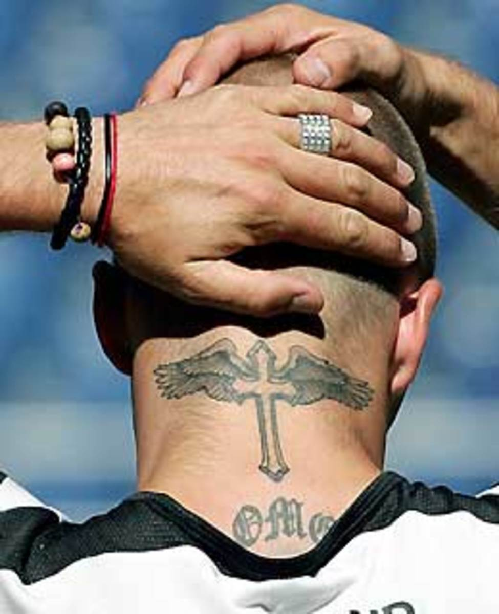 The winged cross on the neck of soccer star David Beckham.  His back is tattooed with a large cross and his right upper arm has a large tattoo of an angel on it.