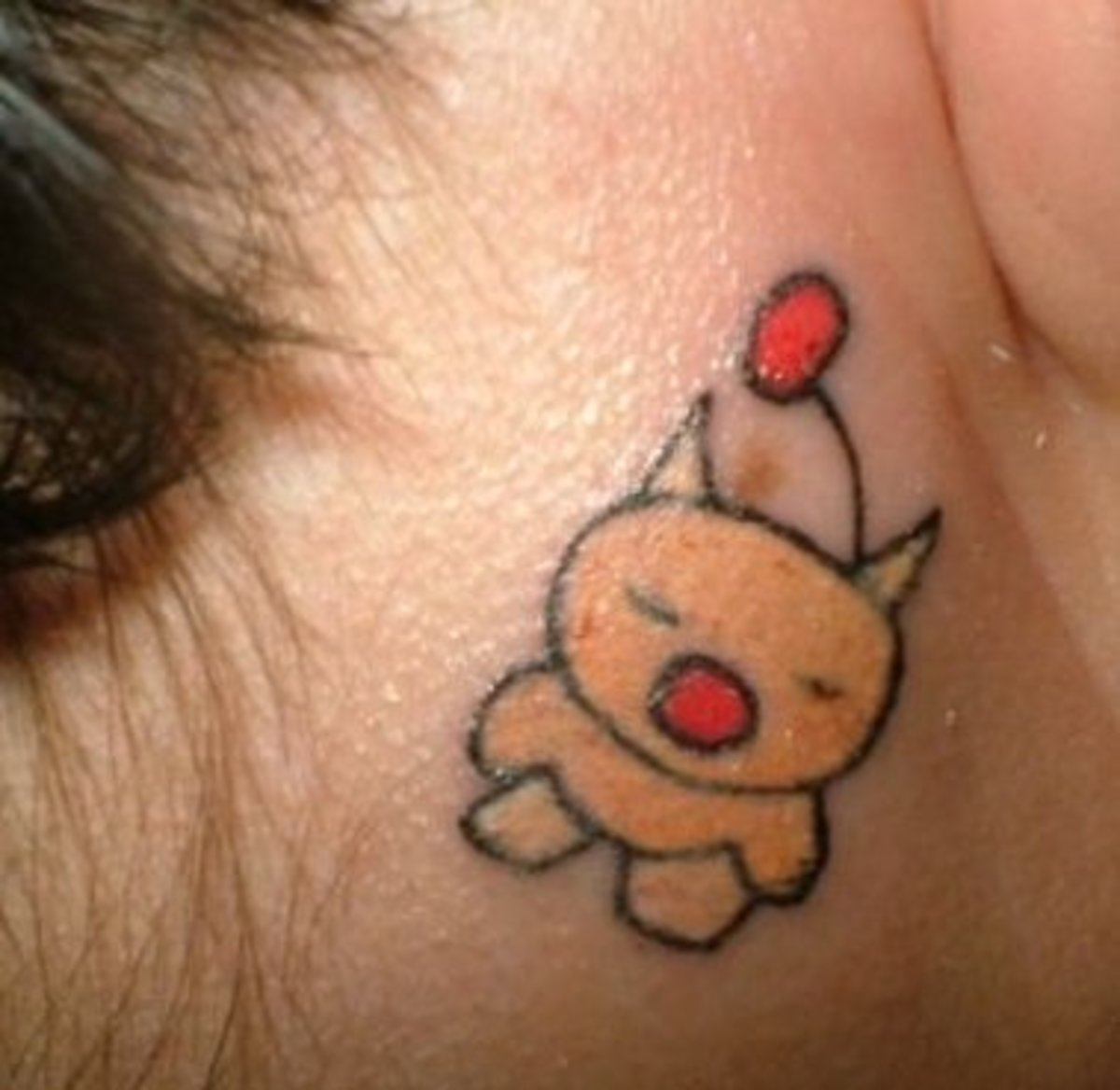 a little animal tattooed behind a person's ear