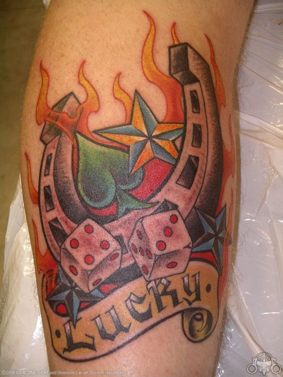A horseshoe, dice, flames, stars, and a spade are depicted in this tattoo.