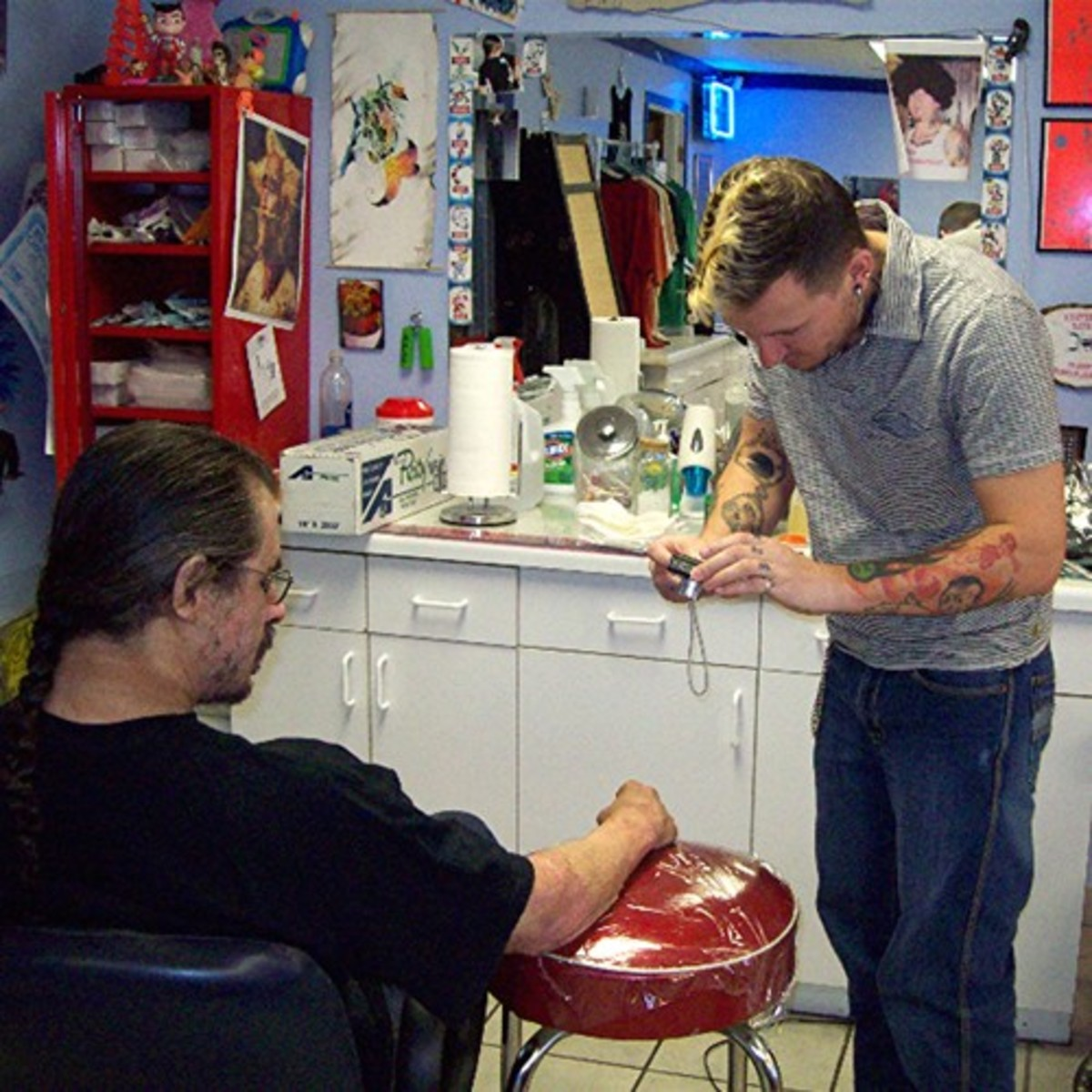 Dang snaps a photo before starting Scott's tattoo.