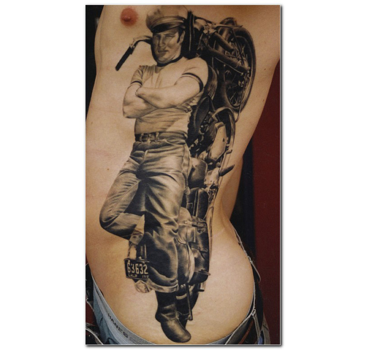 Man lying on motorcycle tattoo