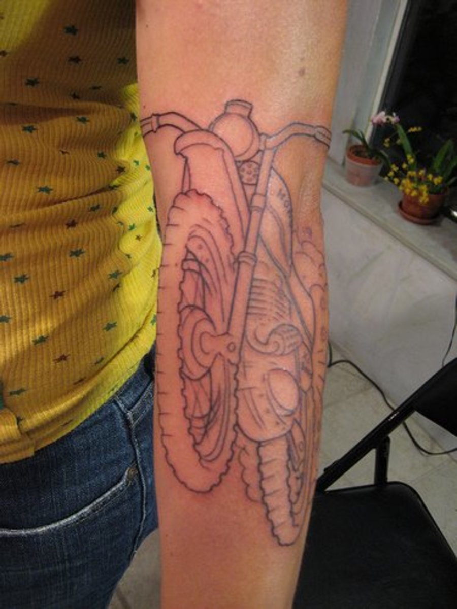 A forearm tattoo of the outline of a motorcycle.