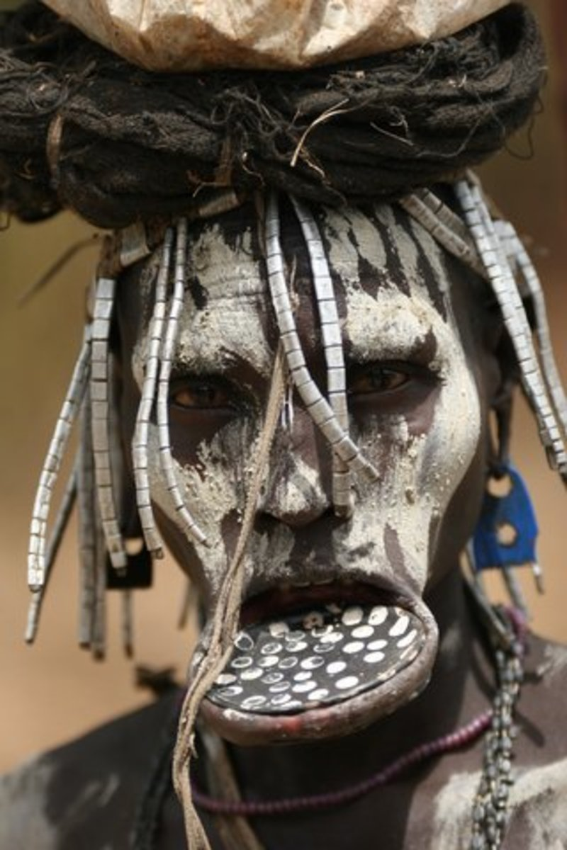 Mursi woman with a lip plate and white paint.