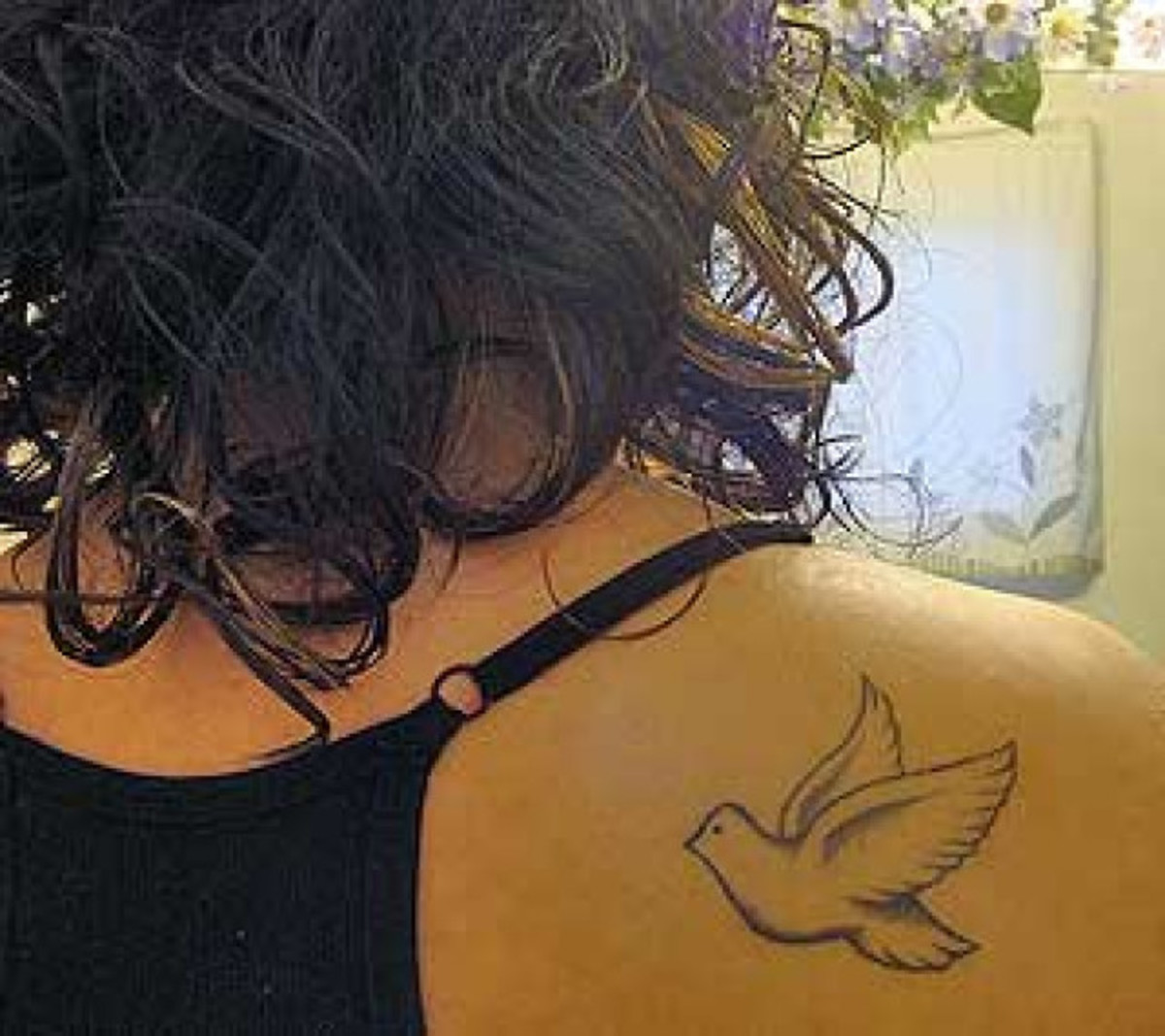 Small dove tattoo on shoulder.