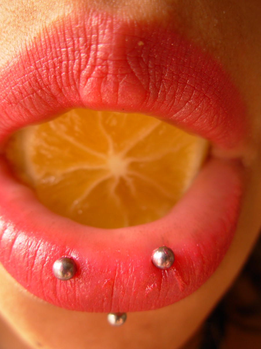 A horizontal labret piercing across the lower lip.