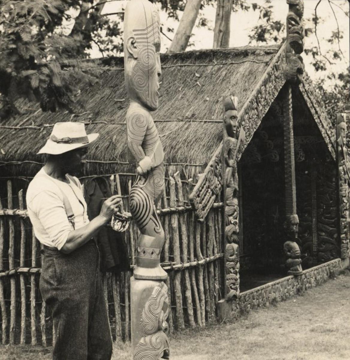A Maori man retouches the tattoo on a tiki sculpture.
