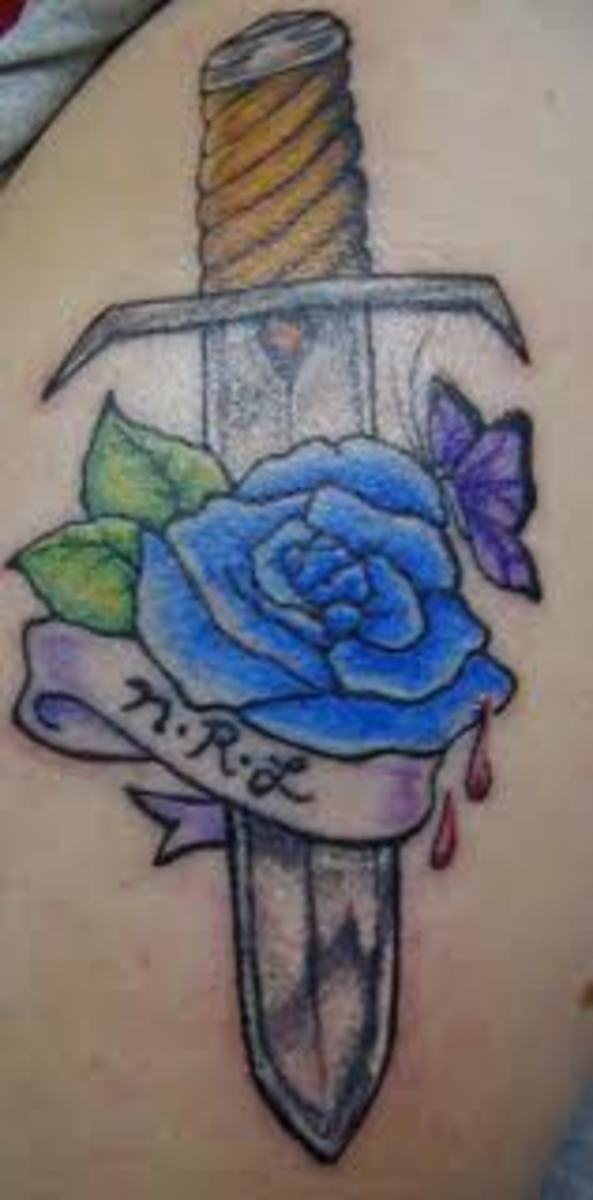 This sword tattoo features a blue rose and a butterfly.