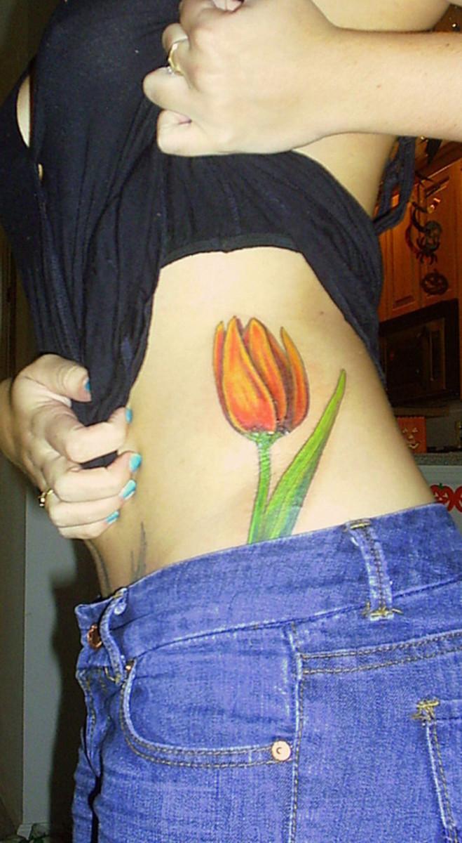 orange tulip tattoo on ribs