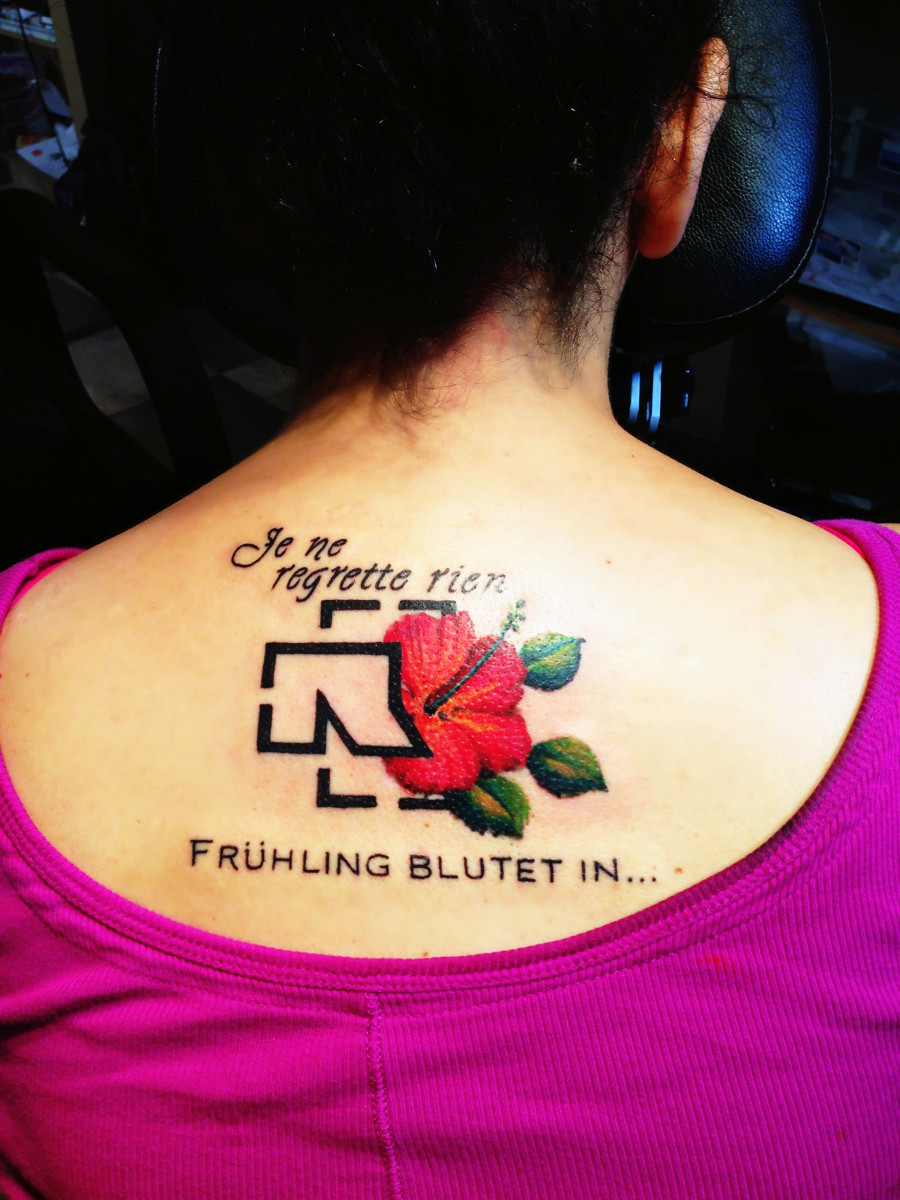 The finished tattoo, with the logo as frame and a painterly flower.