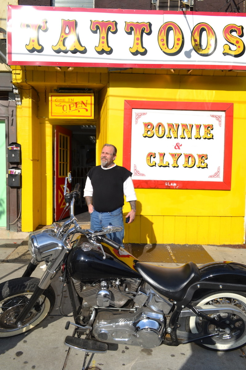 Sailor Eddie, with his motorcycle, in front of his shop, Bonnie & Clyde's Tattoo Parlour.