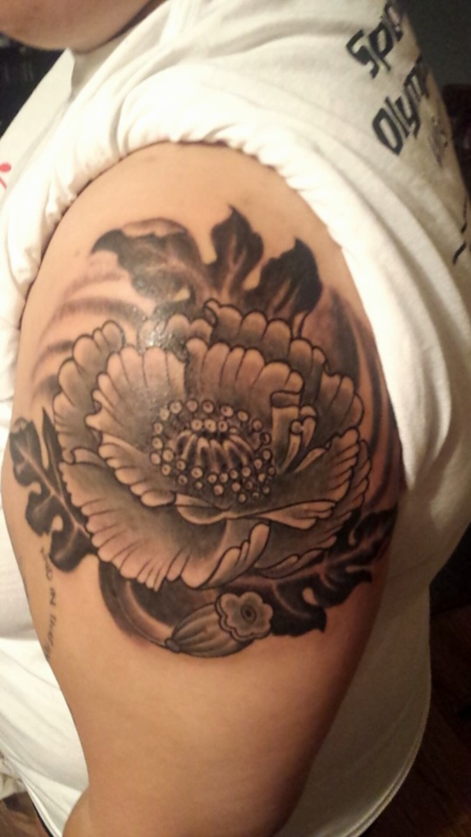 You can expect exquisite detail in a flower of this size. This tattoo was done in black and grey style.