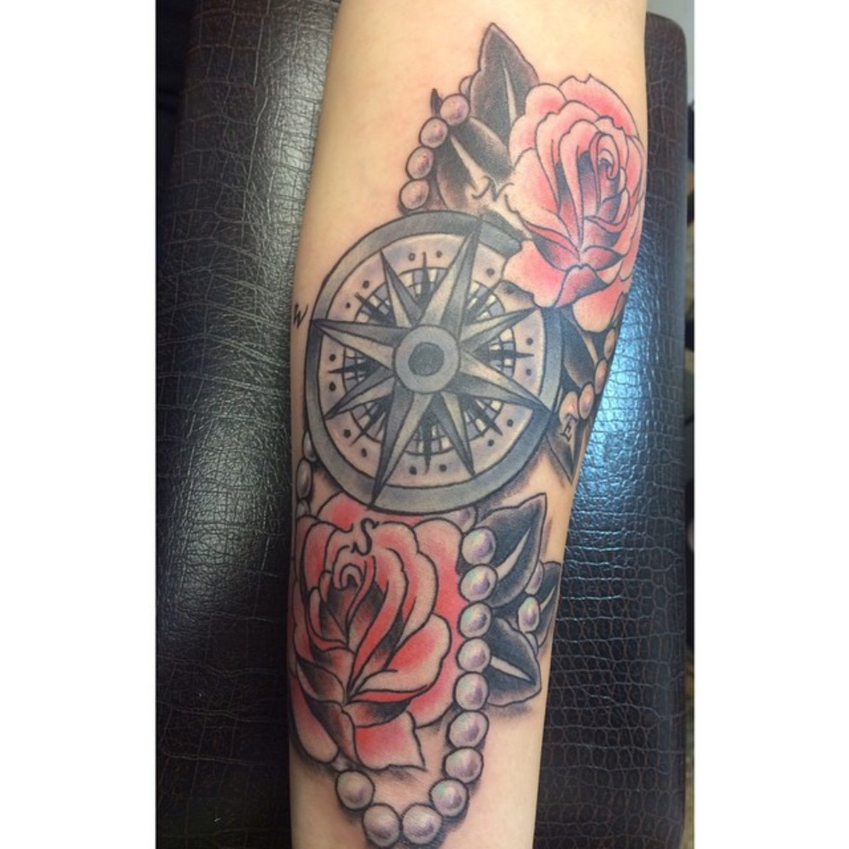 A classic idea for a tattoo with roses and a compass - this one is large enough for beautiful detail.