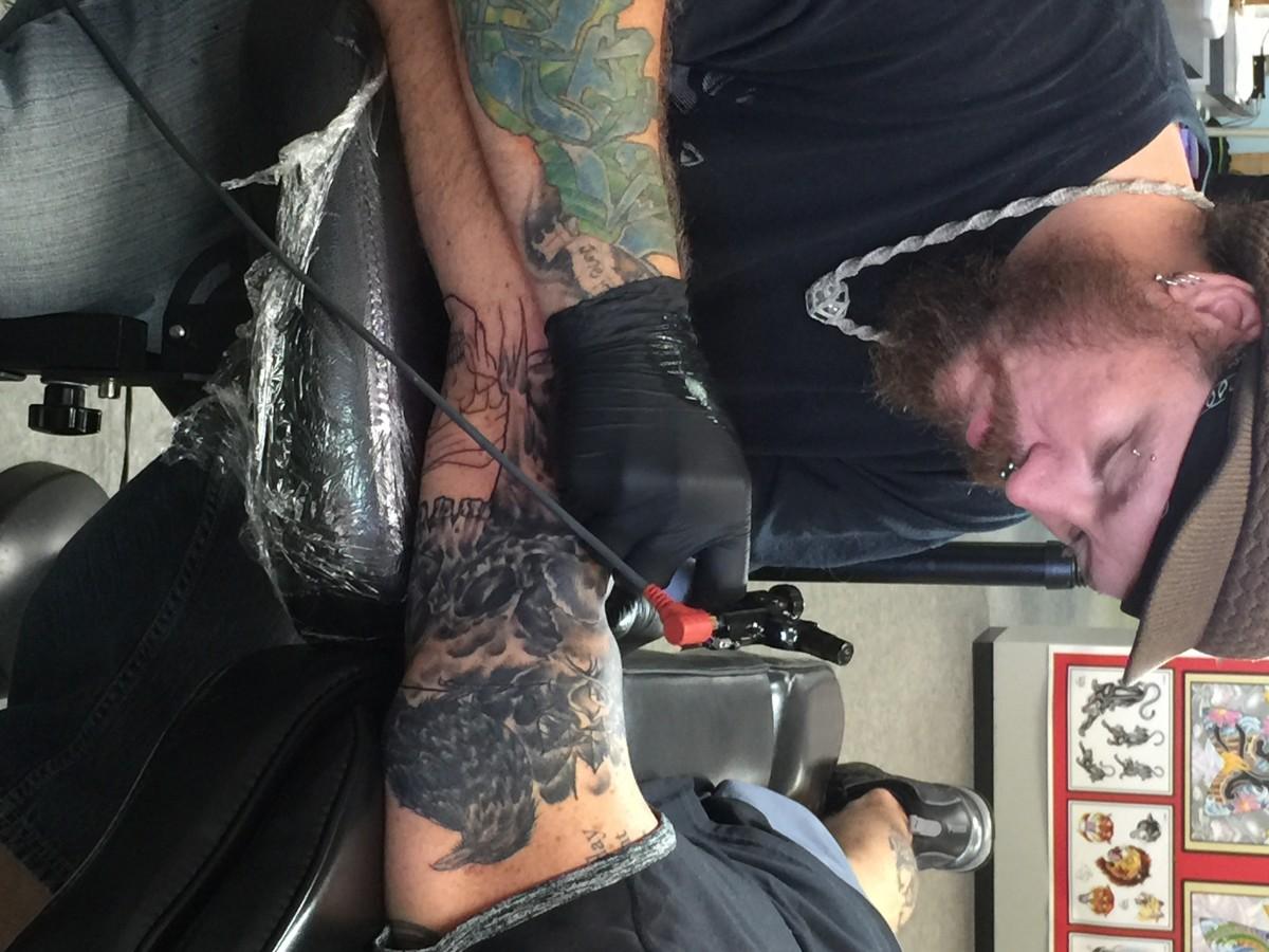 An artist working on a sleeve tattoo.