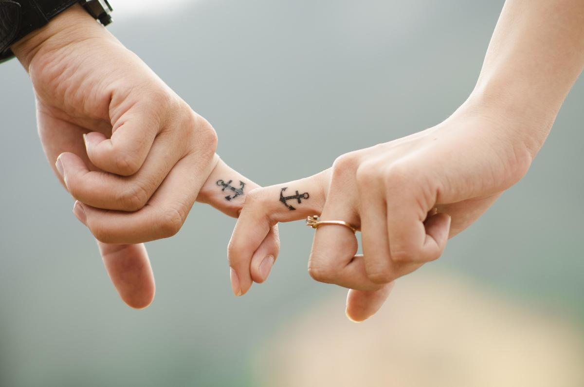 A couple with anchor tattoos on their fingers.
