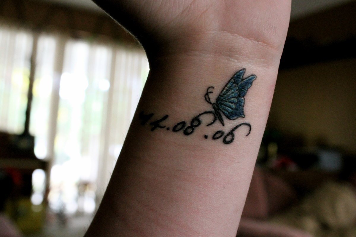 Butterfly tattoo with text.