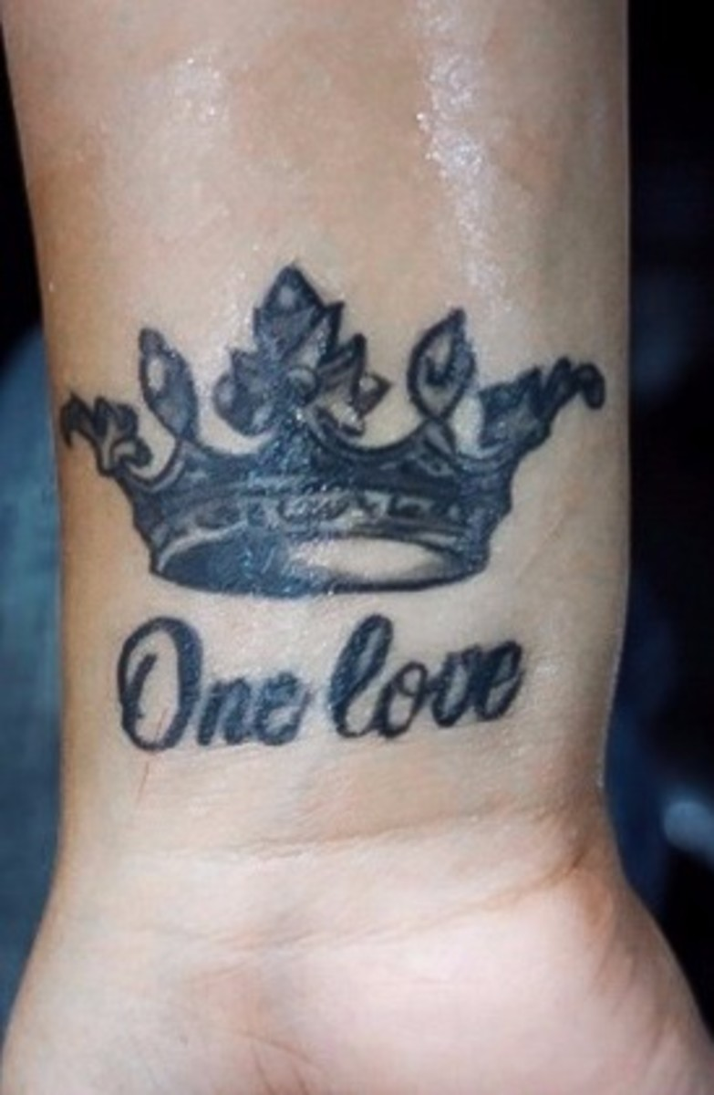 "A crown tattoo with the text ""one love."""
