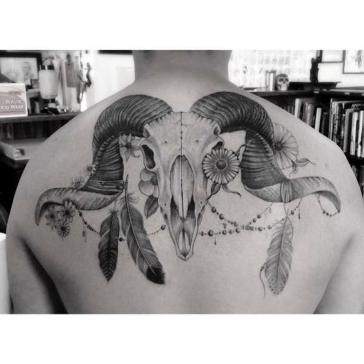 Ram skull Aries tattoo with feathers and flowers
