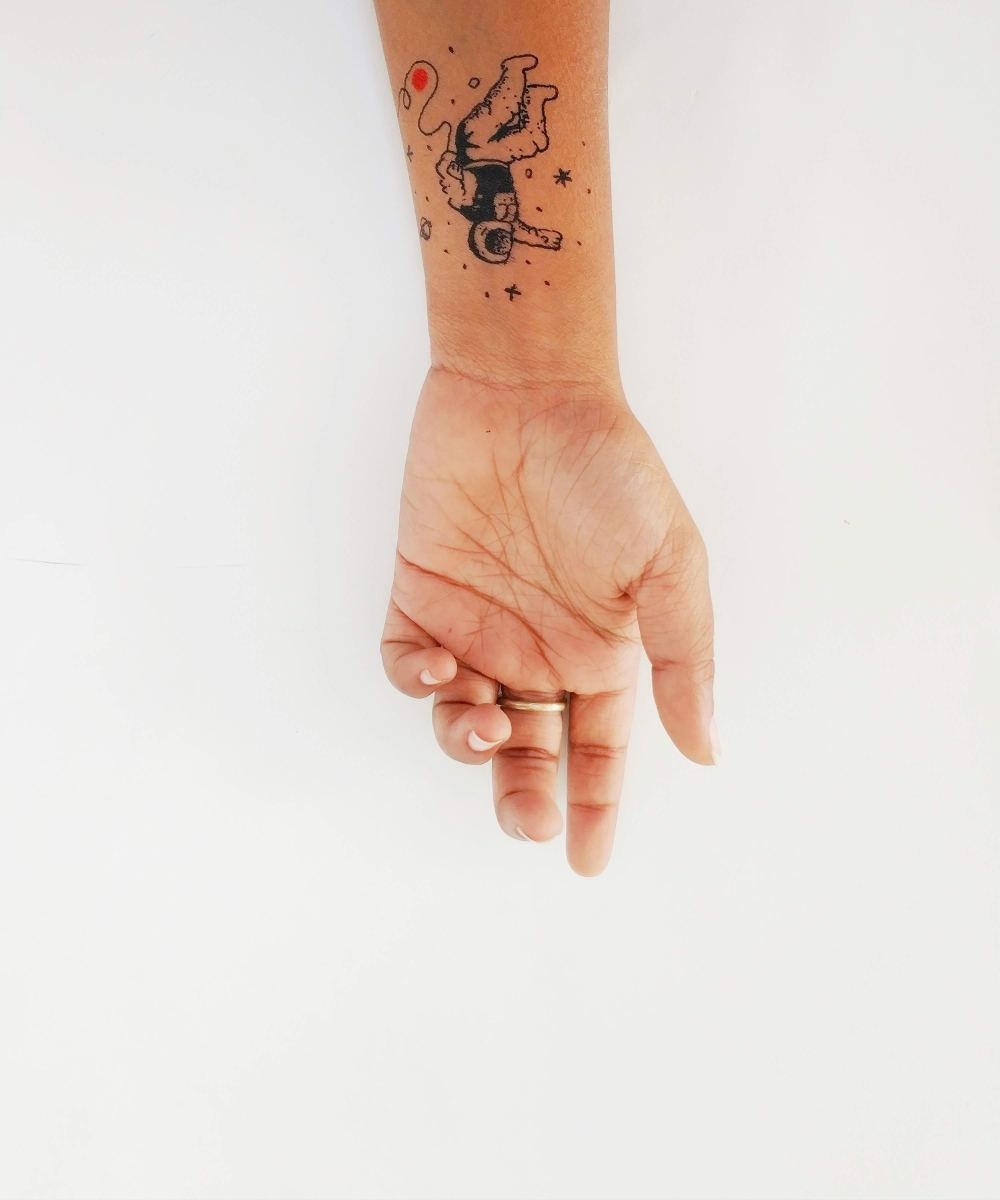 A wrist tattoo reaching for the stars.