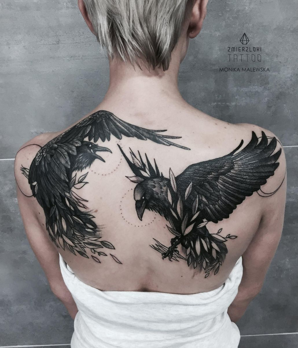 A pair of raven shoulder tattoos.