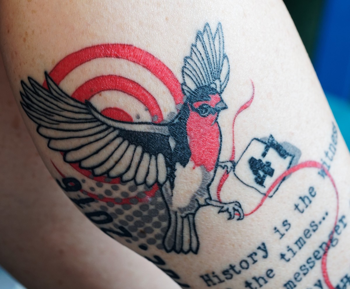 A bird tattoo that incorporates text and other symbols.