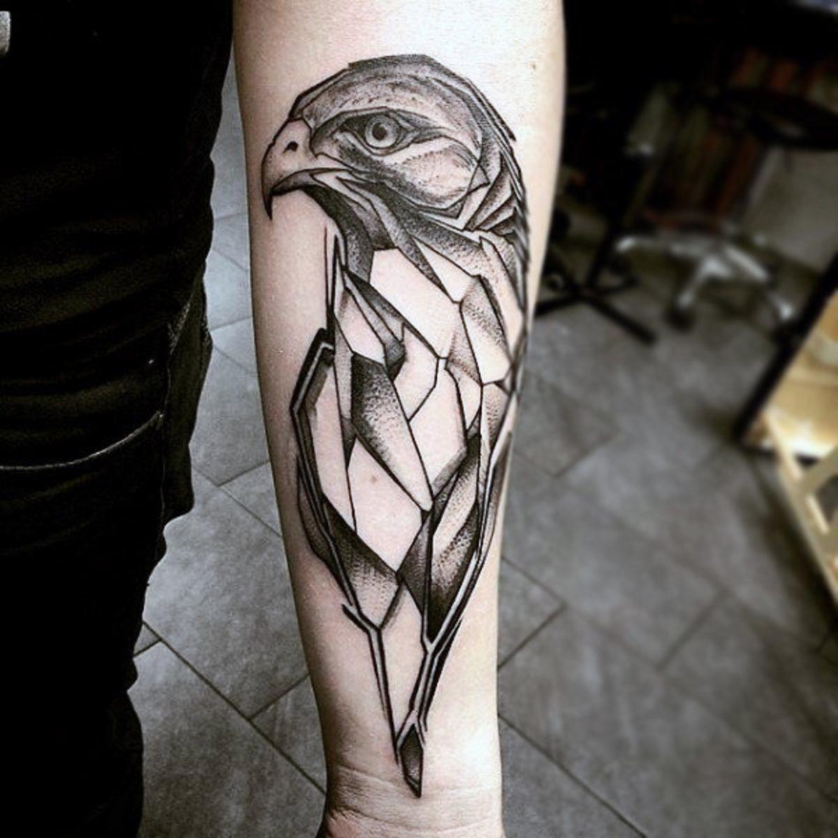 An arm tattoo of a bird of prey.