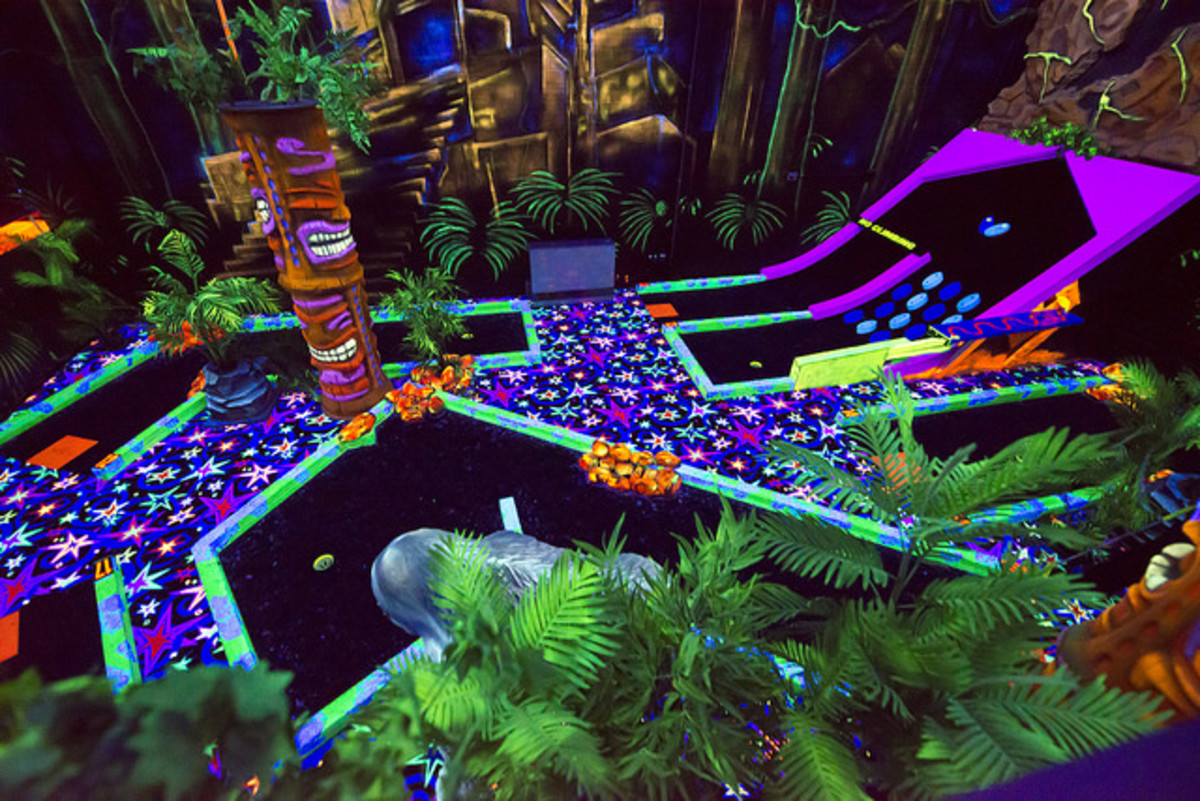 Some mini golf courses are expanding their decor and offering arcades, paintball games, laser tag, and cafes. This one is indoors and features blacklight.