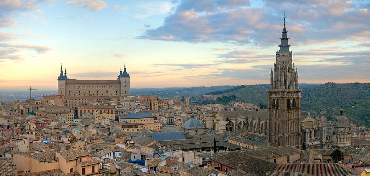 Panorama of the Toledo Skyline in Spain at sunrise. On the left is the Alcázar of Toledo and on the right is the Cathedral of Toledo.