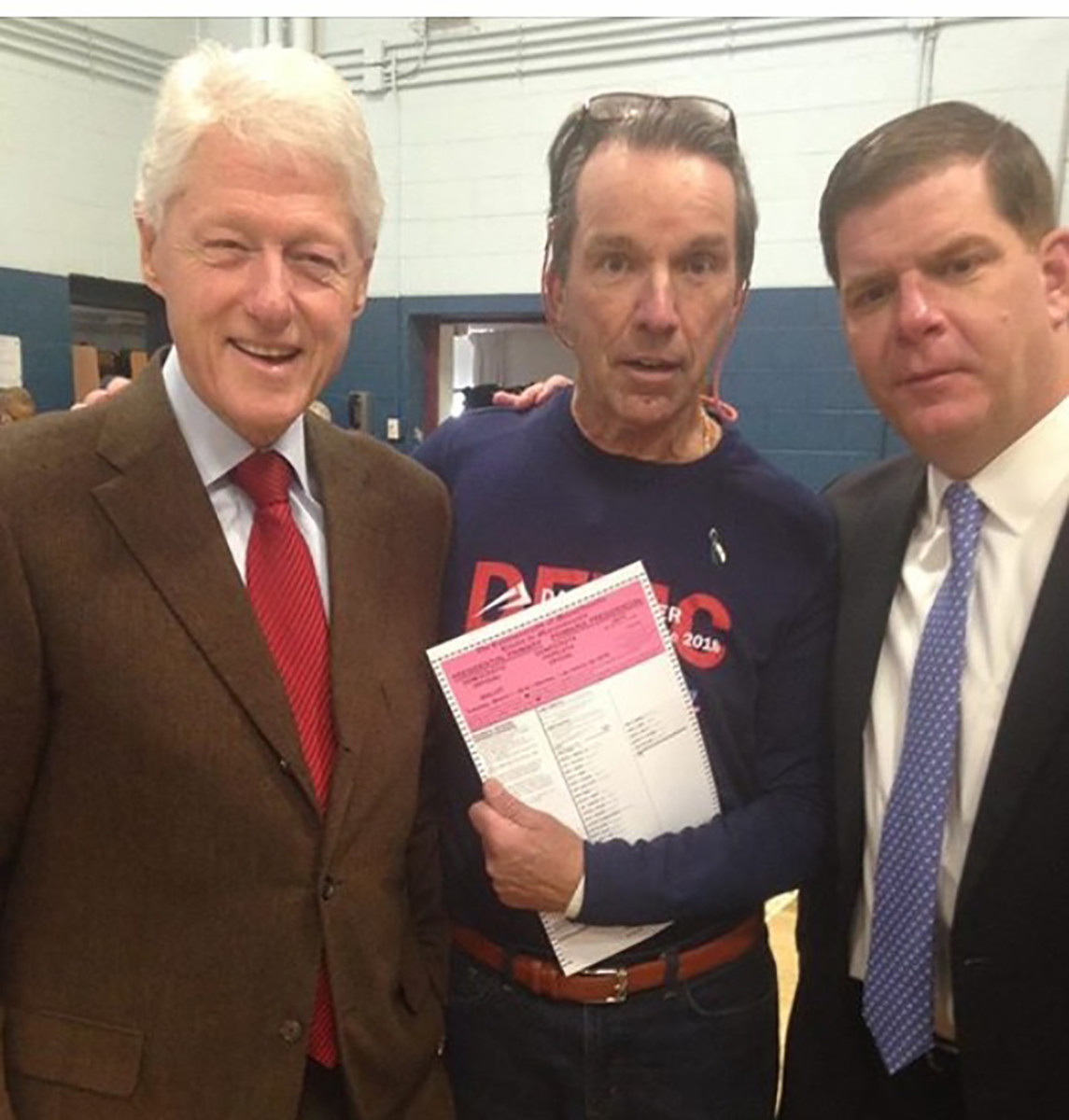 Bill Clinton posing with voter holding ballot inside West Roxbury polling station during voting hours on MA primary day.