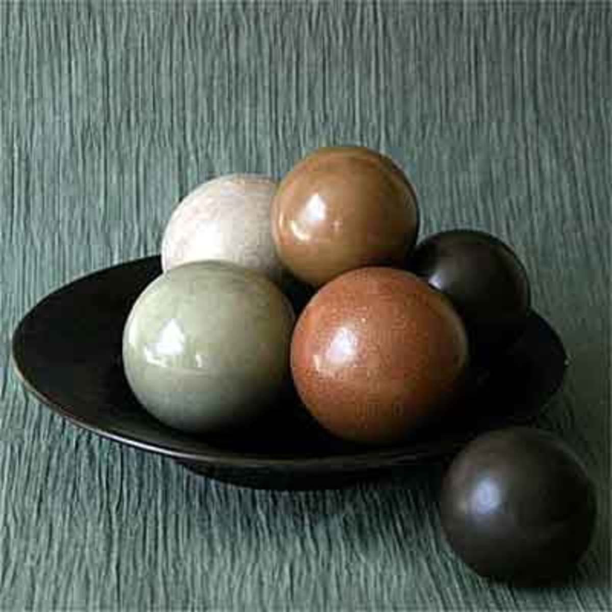 The color of the finished dirt balls comes from the color of the dust or clay used to coat the outside layers of the tightly-compressed ball of mud.