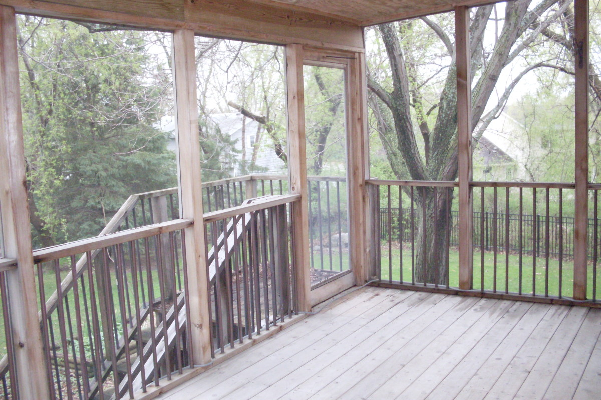 My beautiful cedar deck on a rainy fall day, unstained, clear-coated, and weathered to a nice gray after about two years. I clean the deck annually with dish soap, which usually takes part of an afternoon to sweep and scrub everything down.