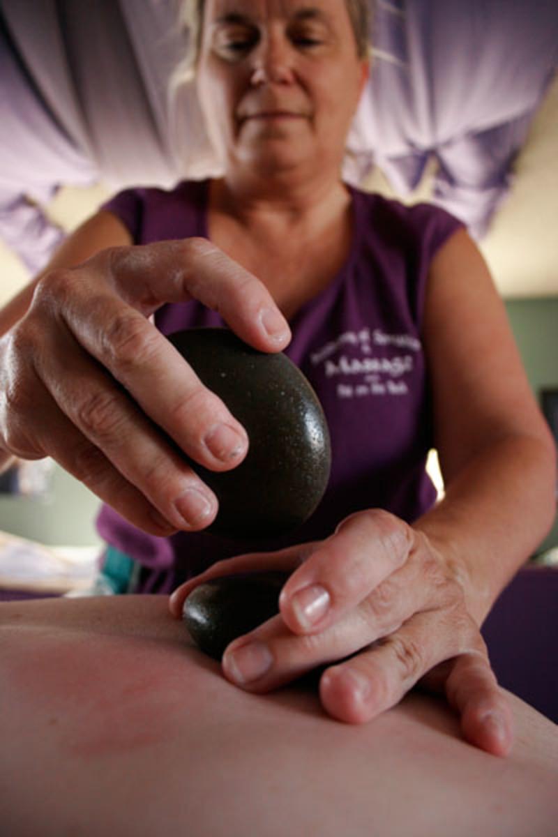 Massage Therapist Places Hot Rocks