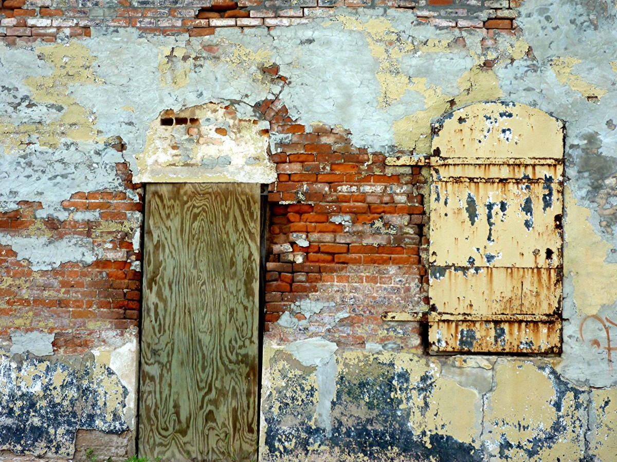 Colorful effects of an exterior old brick and plastered wall in Calvert, Texas
