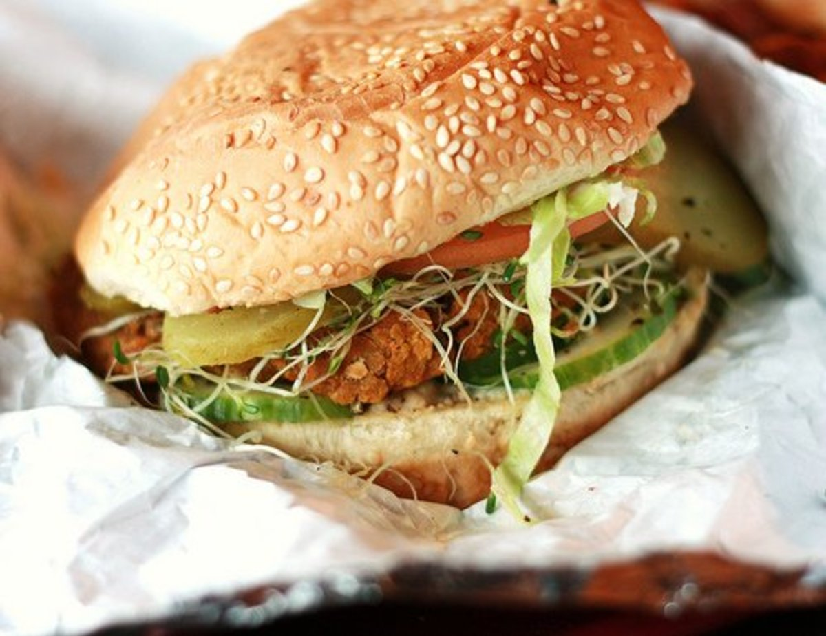A veggie burger with sprouts, pickles, and tomatoes.