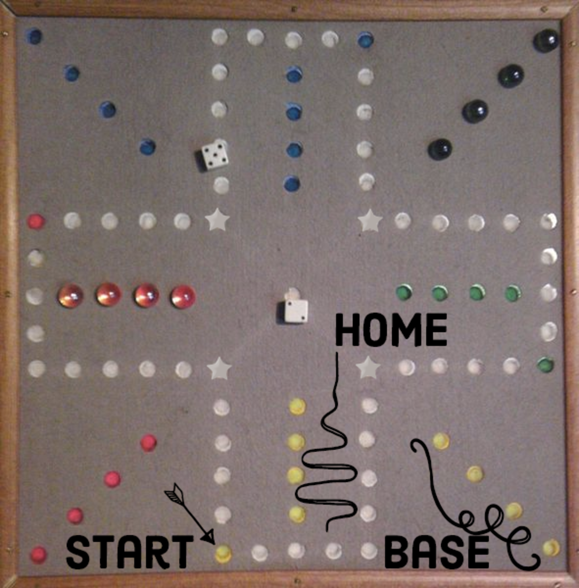 The base row, home row, and start hole are labelled on a homemade Aggravation board. On this board, the red marbles are in the home row, and the green marbles are in the base row.