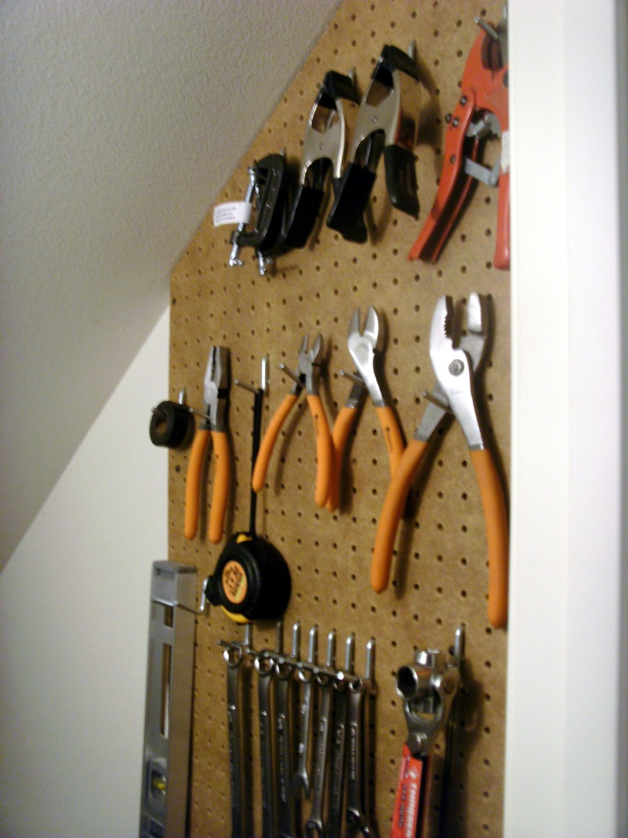 Pegboard tool storage in an under-stairwell closet
