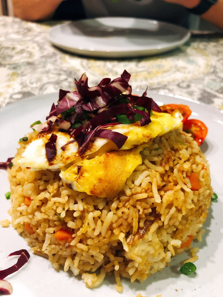 Fried rice with a fried egg and fresh cabbage.