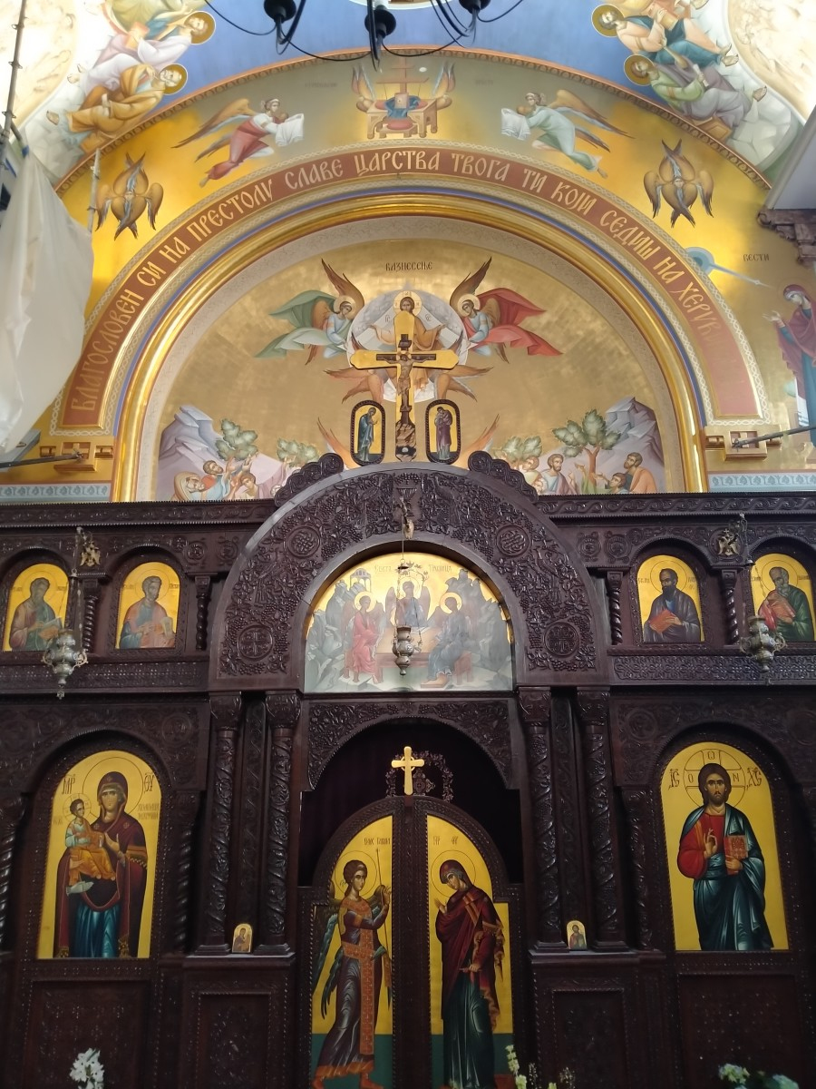 A beautiful, wooden iconostasis with two wings. Usually men light candles on the right and women, on the left hand side of the iconostasis. The gates in the middle represent the doors to heaven. Usually, I see Archangel Michael over the main arc.